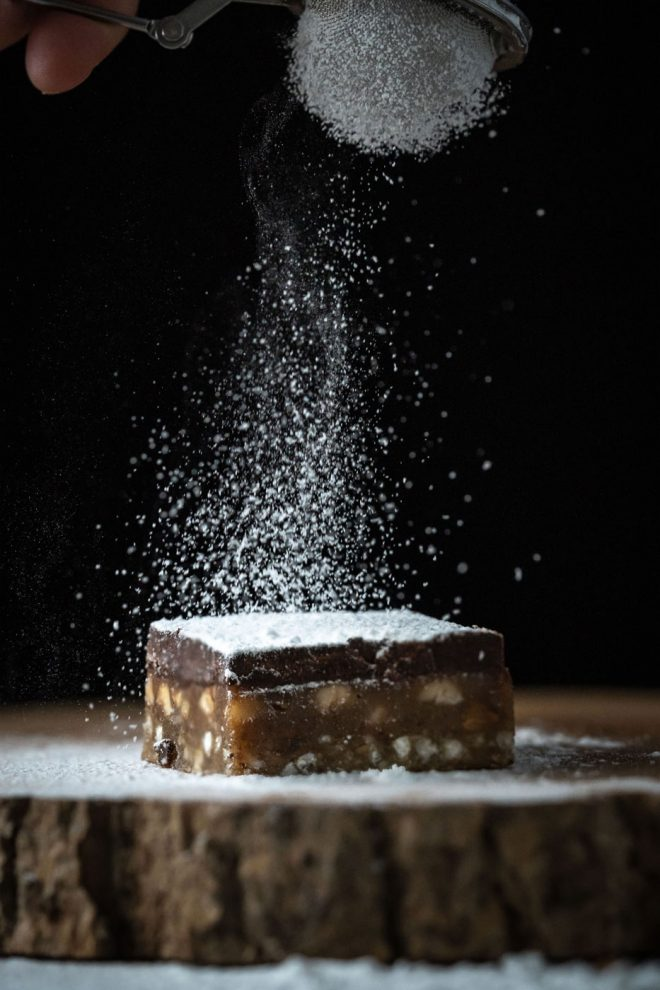 Photo of sprinkling powdered sugar on brownie bar, photograph by Lauren Caris Short of Food Photography Academy