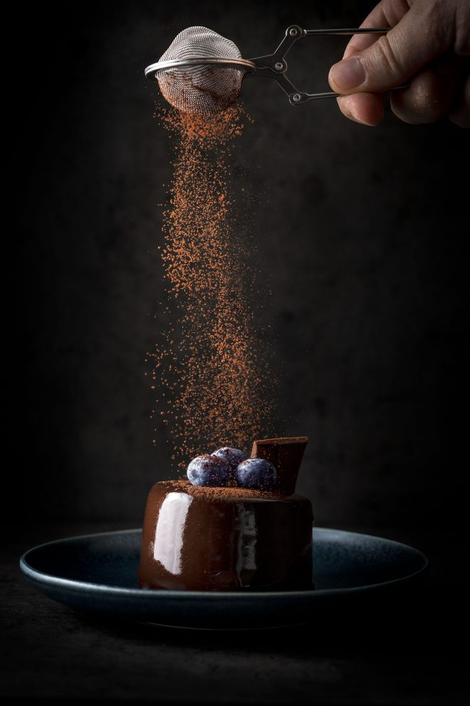 Cacao powder sprinkled on top of glazed chocolate cake with blueberries, photograph by Lauren Caris Short of Food Photography Academy