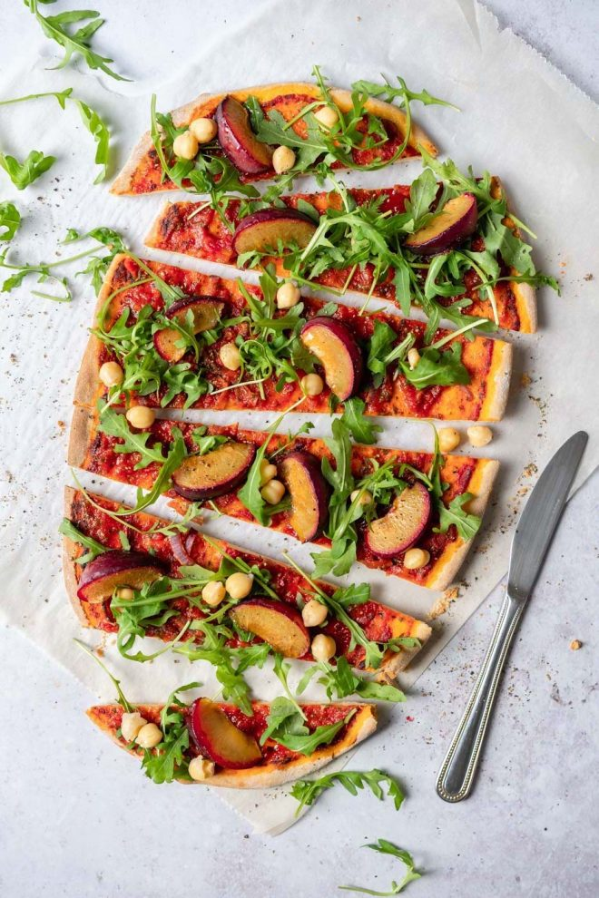 Flatlay of a flatbread with peaches, tomato sauce and arugula, photograph by Lauren Caris Short of Food Photography Academy""