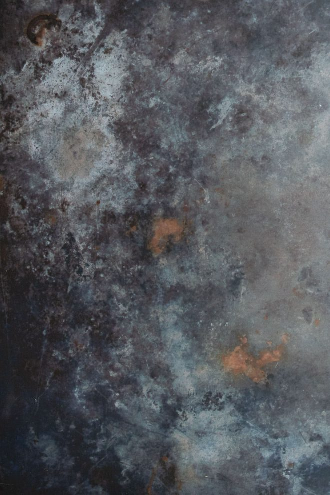 Close up shot of a marbled backdrop of dark gray, light gray, and copper tones.photograph by Lauren Caris Short of Food Photography Academy