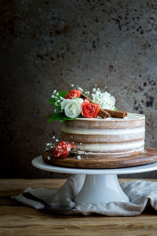 Naked cake with flowers and cinnamon sticks photographed head-on, photograph by Lauren Caris Short of Food Photography Academy
